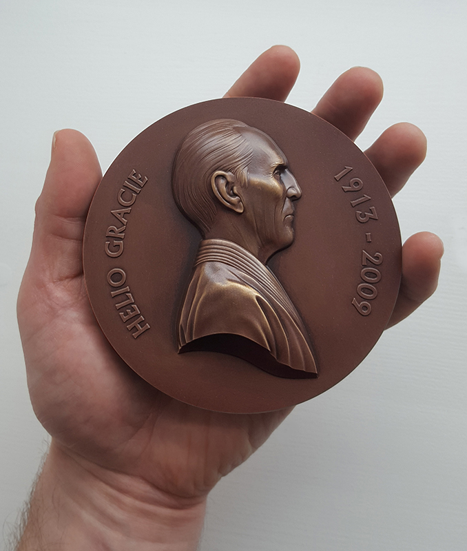 Jiu Jitsu art - Jody Clark (artist) holding bronze medal with Helio Gracie on it